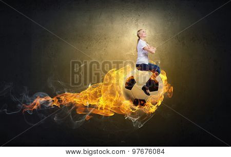 Young woman sitting on burning soccer ball