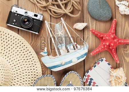 Travel and vacation items on wooden table. Top view