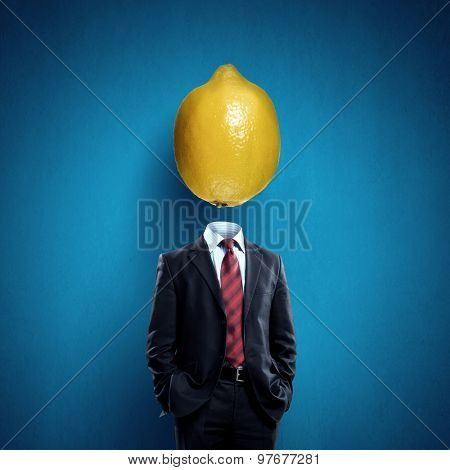 Headless businessman with lemon instead of head
