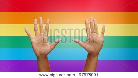 people, gay pride and homosexual concept - palms of african american human hands over rainbow flag stripes background