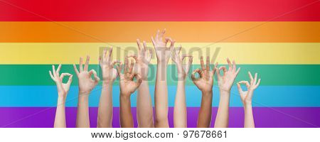 people, gay pride, gesture and homosexual concept - human hands showing ok sign over rainbow flag stripes background