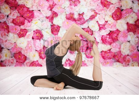 sport, fitness, yoga, people and health concept - happy young woman doing headstand exercise on wooden floor over wall of flowers background