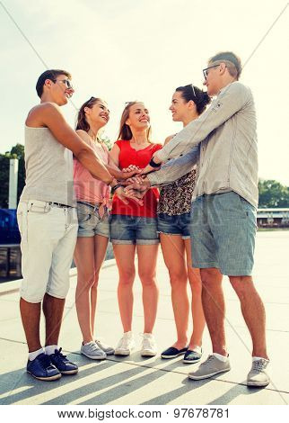 friendship, leisure, summer, gesturer and people concept - group of smiling friends with hands on top in city