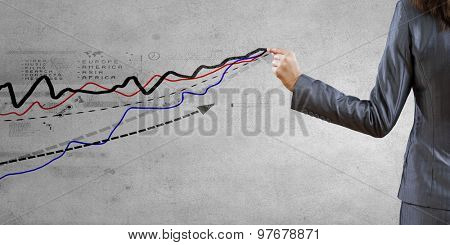 Rear view of businesswoman drawing increasing arrow graph