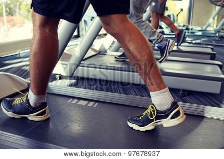 sport, fitness, lifestyle, technology and people concept - close up of men legs walking on treadmills in gym