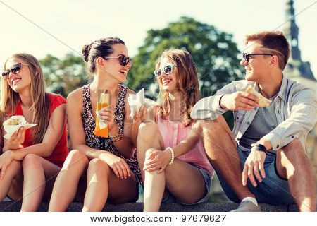 friendship, leisure, summer and people concept - group of smiling friends in sunglasses sitting with food on city square