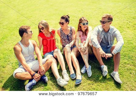 friendship, leisure, summer and people concept - group of smiling friends outdoors sitting and talking on grass on grass in park