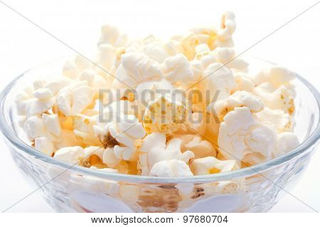 Popcorn in a glass bowl, isolated on white