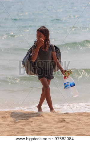 An Unidentified Girl Collects Plastic Bottles At The Seaside