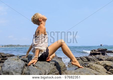 Young Woman In White And Back Cloths Sitting On Rocky Seashore