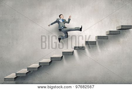 Young businessman walking up on staircase representing success concept