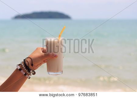 Female Hand Holding Milk Shake With Tropical Sea View Background