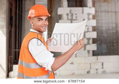 Cheerful young foreman is working with sketches of construction