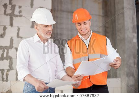 Cheerful construction team is working on plan of building