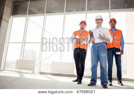 Cheerful skilled builders are meeting their client