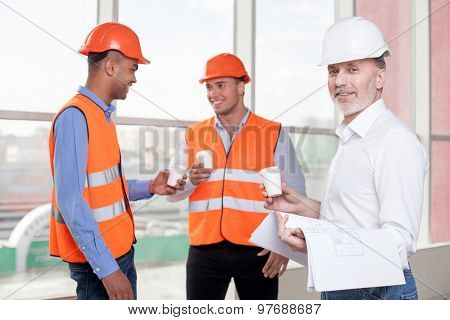 Successful friendly construction team is relaxing on break