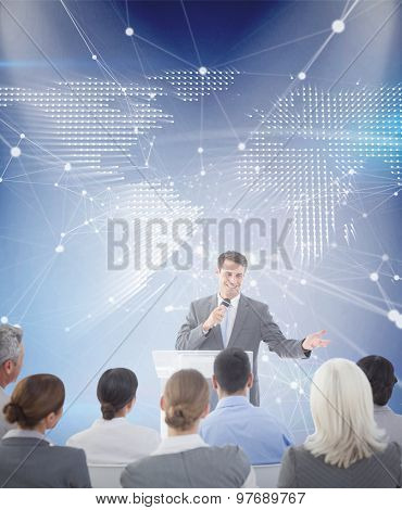 Businessman doing speech during meeting against glowing world map on black background