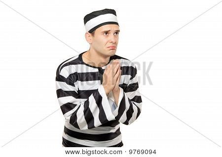 A Sad Prisoner With Both Hands Clasp In Begging Gesture