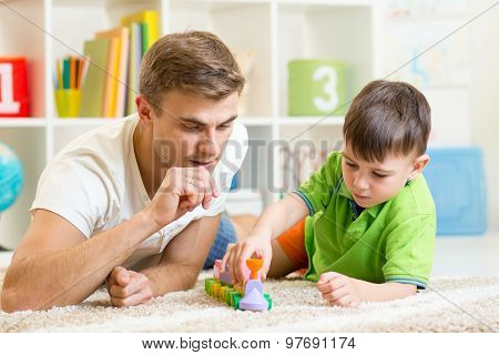 Father And Son Playing With Blocks At Home