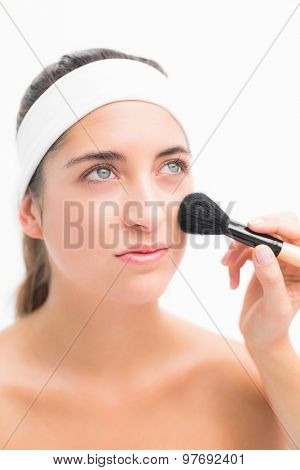 Close up of a hand applying blush to beautiful woman
