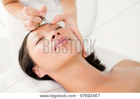 Close up view of woman using tweezers on patient eyebrow at the health spa