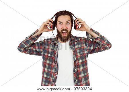 Handsome hipster enjoying listening to music on white background