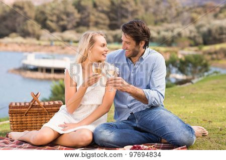 Cute couple on date toasting with glass of white wine