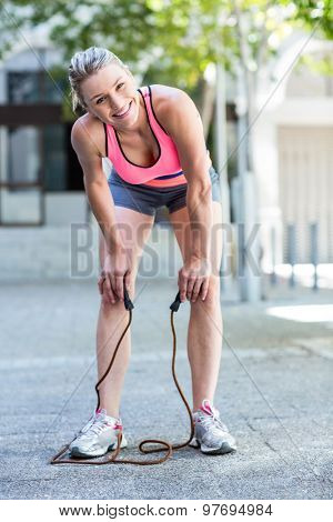 A pretty woman doing jumping rope on a sunny day