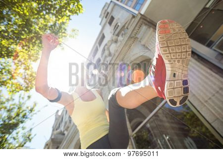 A pretty woman jumping in the street on a sunny day