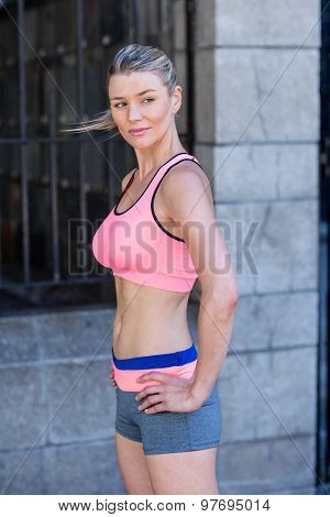 A beautiful athlete with her hands on her hips on a sunny day