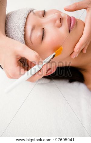 Side view of an attractive young woman receiving massage at spa center