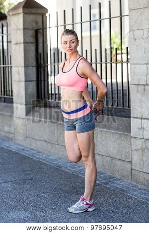 A beautiful woman stretching her leg against a fence on sunny day