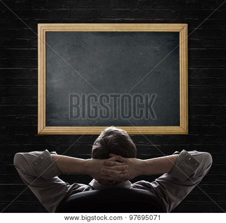 Concept of businessman looking at blank blackboard
