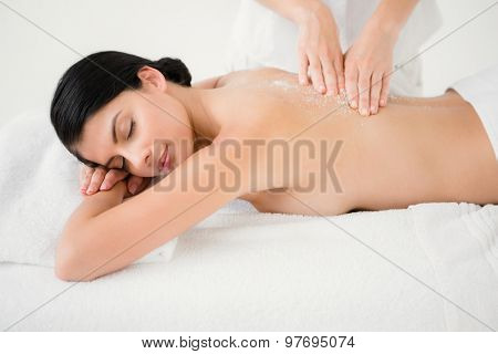 Side view of woman receiving a salt scrub massage at spa center