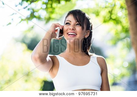 Smiling athletic woman phoning with smartphone in the city