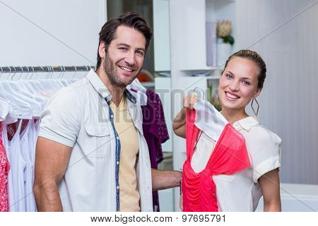 Portrait of smiling woman showing red dress to boyfriend in clothing store