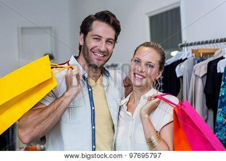 Smiling couple with shopping bags in clothing store