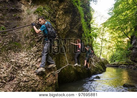 Hikers Climbing Above The River