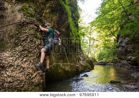 Hiker Climbing Above The River
