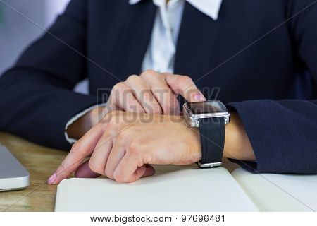 Businesswoman using her smartwatch at desk in her office
