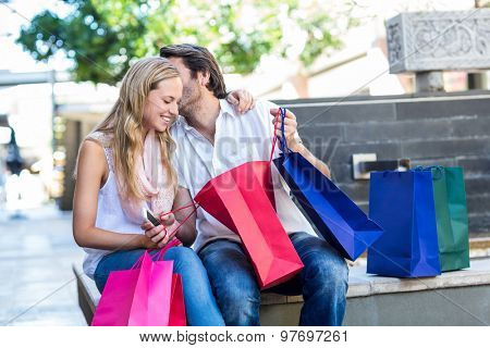 Smiling man with shopping bags kissing his girlfriend while sitting on bench at shopping mall