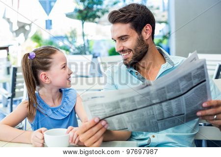 Happy father and his daughter having breakfast together in the cafe