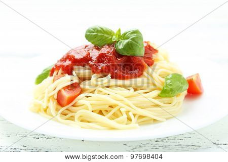 Spaghetti With Tomatoes And Basil On Plate On White Wooden Background
