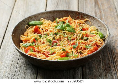 Spaghetti With tomatoes and basil on wooden table