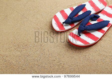 Pair Of Flip Flops On Sand Beach
