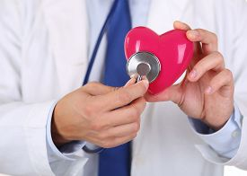 pic of resuscitation  - Male medicine doctor holding red heart and putting stethoscope head close to it closeup - JPG