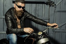 picture of biker  - Handsome brutal unshaven male biker with long beard in brown leather jacket jeans and sun glasses sitting in garage on motorcycle looking forward on grey wooden background horizontal picture - JPG