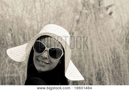 Girl with hat and eyeglasses and willow in the background