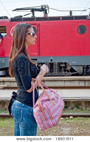 Girl with bag waiting for train with loco in the background