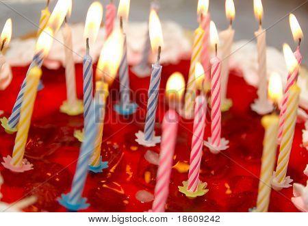 Pastel de celebración y ardientes velas (dof superficial)
